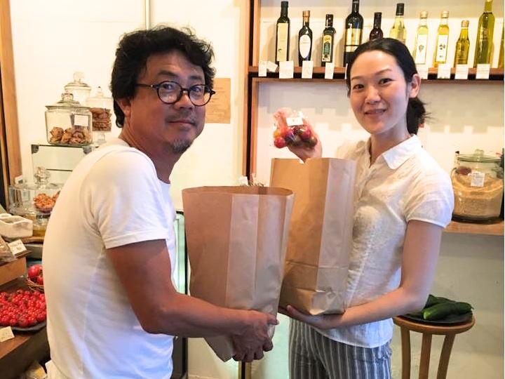 「ごちそうじかん」主催の山崎さん(右)に野菜を渡す大皿さん。ピックアップステーションにて。